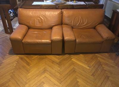 Poltrone in pelle arancione con divano